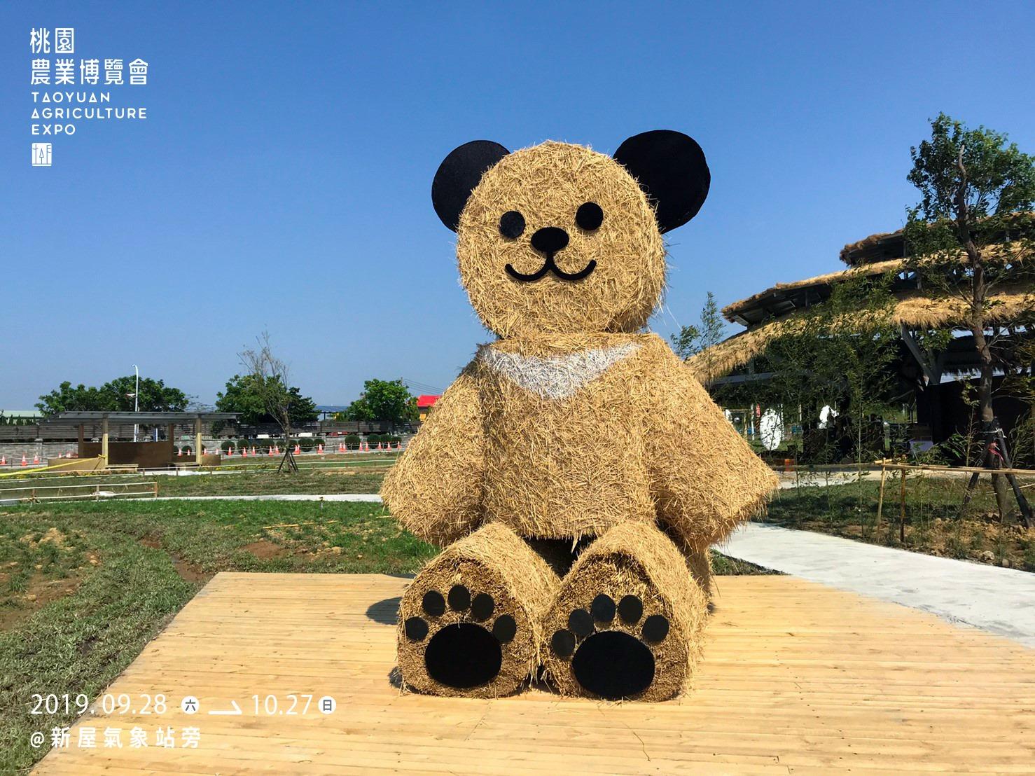 巨大稻草熊坐在草地上,從遠方就吸引遊客目光,老中青經過都忍不住上前跟它合照留念。圖:翻攝自農業博覽會官方臉書