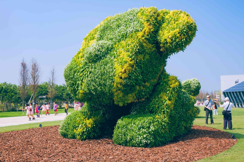農博會的狗狗「阿綠」在上一屆農博會也有亮相,這一屆換上的是全綠衣服,在臉上點綴幾朵黃花。圖:謝佳真/攝
