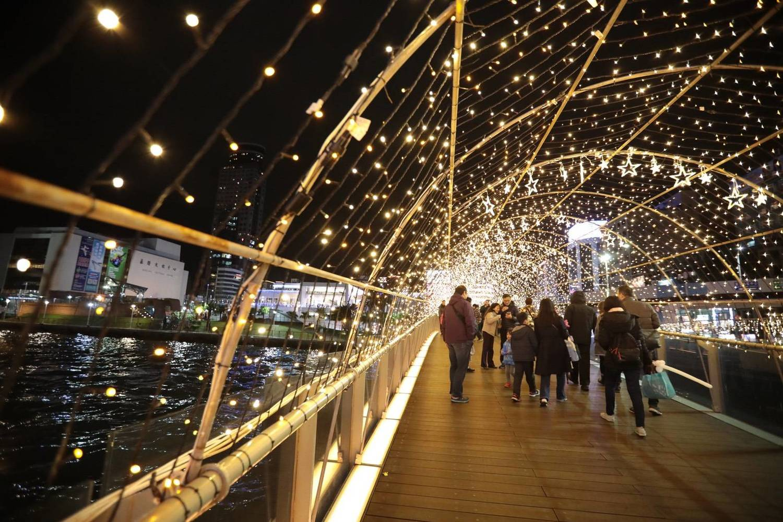 基隆市府將海洋廣場打造成耶誕廣場,在海風吹拂下於燈海隧道下散步。圖:基隆市政府/提供