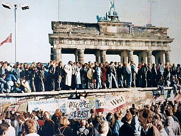 在隔離牆被拆除前數日,德國人站在勃蘭登堡門(Brandenburg Gate)前的隔離牆頂部。 圖:取自維基百科
