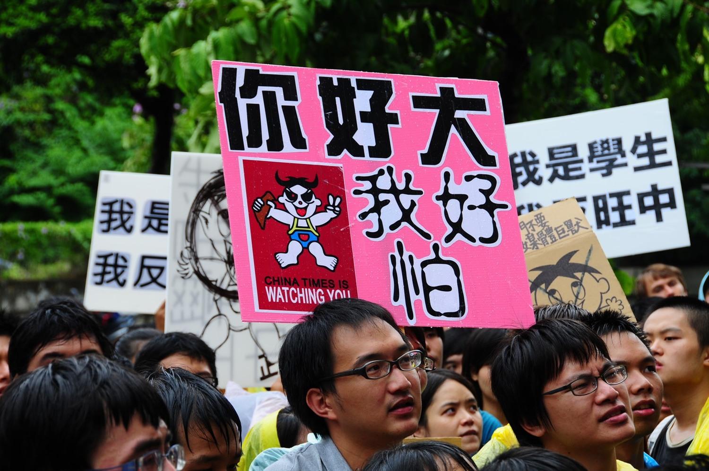 反旺中併購的學生遊行中,有人高舉「你好大,我好怕」牌子。