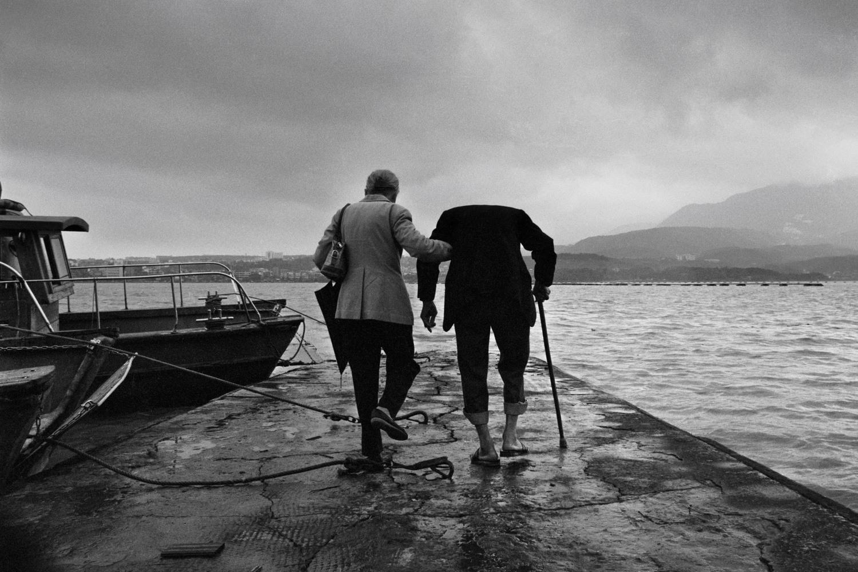 1988年4月,一對老夫婦走在八里渡船頭上,準備搭船去對岸的淡水。 圖:張良一/攝