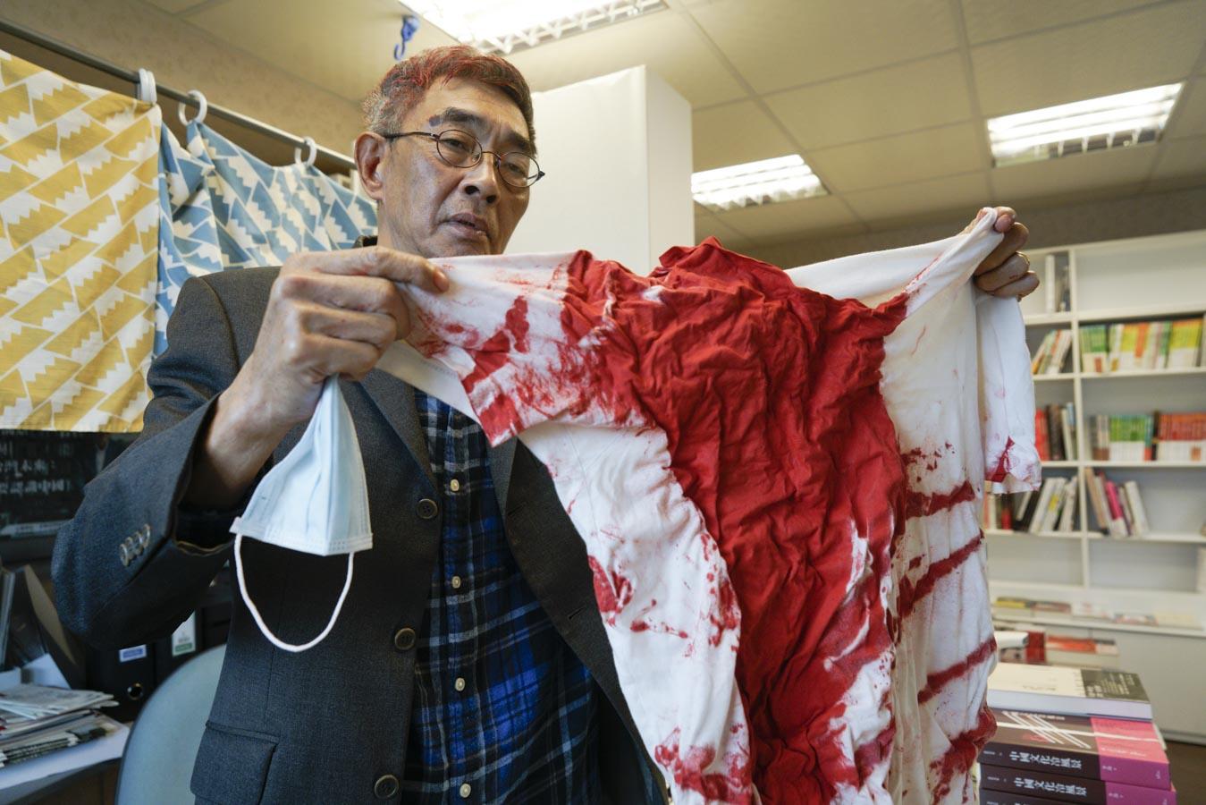 中山銅鑼灣書店負責人林榮基出示日前被潑灑紅色油漆的上衣,令人觸目驚心。圖:張良一/攝