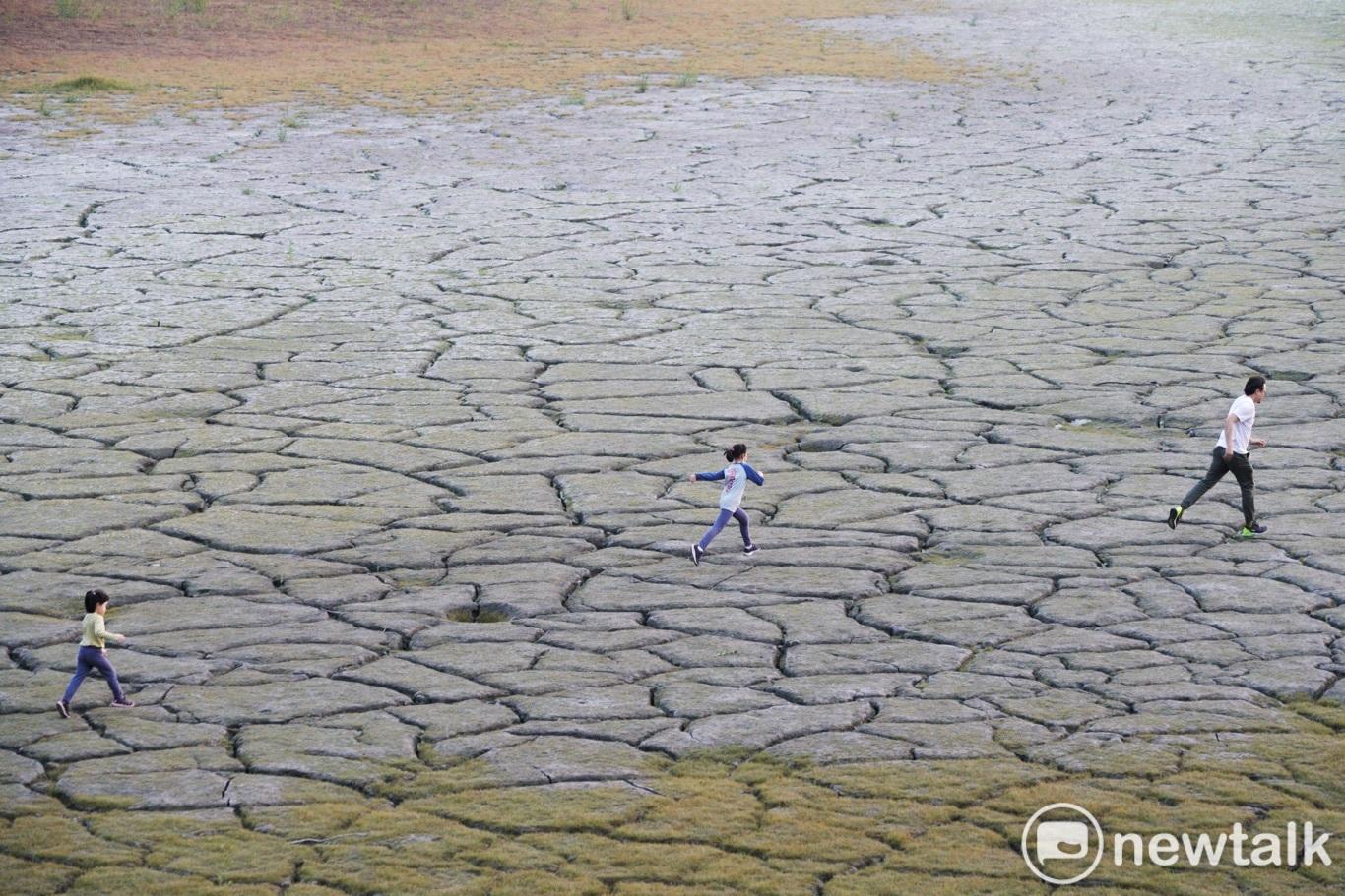 一位爸爸帶著孩子在已然變成日月潭大草原的大竹湖一帶湖底奔跑。圖:張良一/攝
